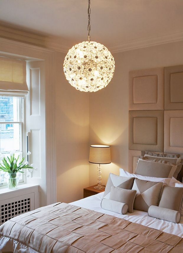 Ceiling light above double bed with upholstered headboard