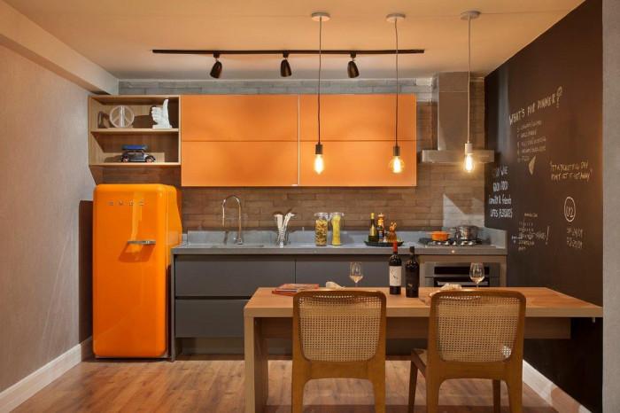 decoracao de sala jovem:Na cozinha, a geladeira e armário superior em laranja contrastam com